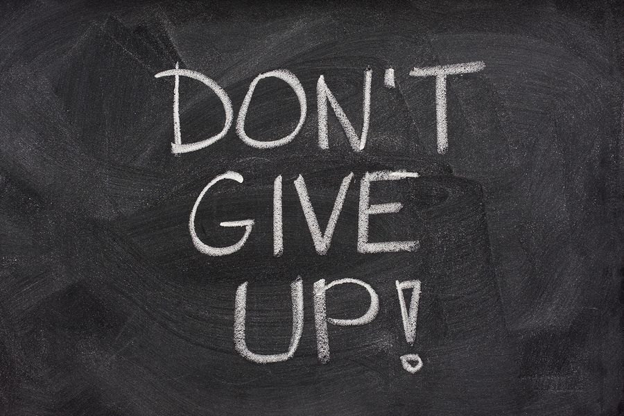 motivational phrase, don't give up, handwritten with white chalk on a blackboard